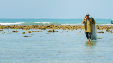PHUKET. THAILAND - CIRCA NOV 2014: Local fisherman wades in shallow waters looki Footage
