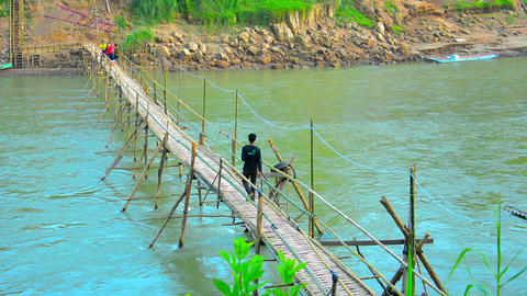LUANG PRABANG. LAOS - CIRCA DEC 2013: Handmade bamboo bridge provides access for Footage