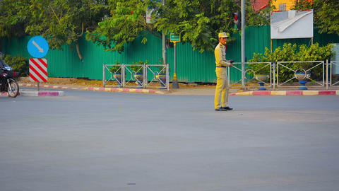 Police officer directing traffic on a typical intersection in Vientiane. Laos Footage