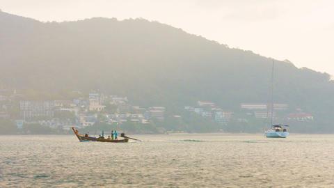 KAMALA. PHUKET. THAILAND - CIRCA DEC 2014: Local fishermen cruise by on a handma Live Action