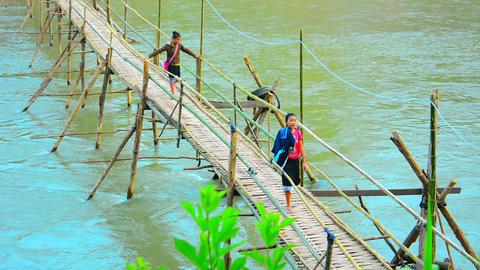 Native Girls Crossing a Handmade Bamboo Bridge in Laos Footage