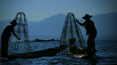Silhouettes of fishermen at sunset. In the evening they go home Footage