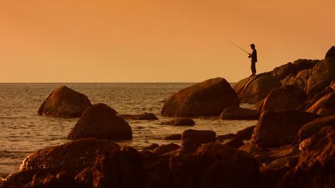 KAMALA. PHUKET. THAILAND - CIRCA DEC 2014: Silhouette of angler. fishing from th Footage