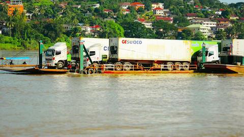 HUAY HAI. LAOS - CIRCA DEC 2013: Tractor-trailer cargo trucks being floated upri Footage