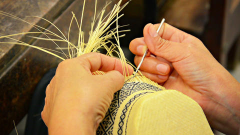 Local Artisan Weaving Colorful Patterns into Straw Basket Footage