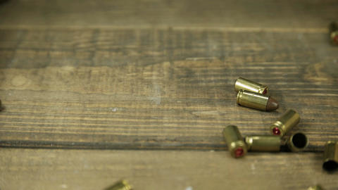 9mm bullet casings falling onto wooden floor 4 K UHD Archivo