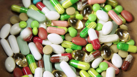 Assortment Of Colorful Pills Accumulating In Wooden Bowl stock footage
