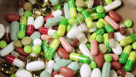 Multitude of colorful pills and tablets piling up Footage
