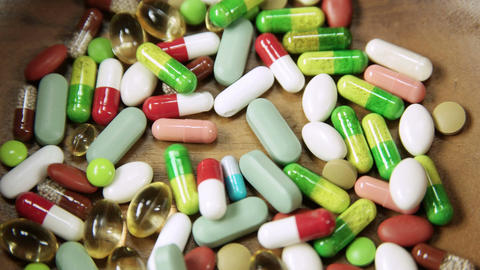 Multitude of colorful pills and tablets piling up 4 K UHD Archivo