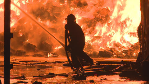 Firemen fighting a large industrial fire Stock Video Footage