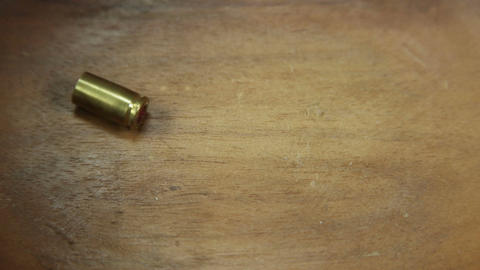 Single bullet cartridge falling and coming to rest on wooden floor Archivo