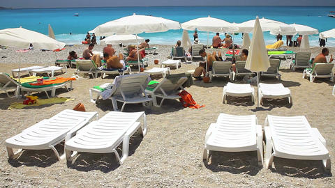 Beach with tourists, sunbeds and umbrellas. Summer, holidays and vacation concep Footage