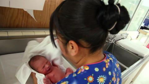 Mexico: MEDIUM SHOT-BACK SHOULDER. Nurse dried a newborn with a towel Footage