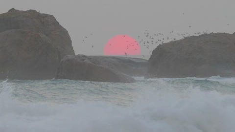 red sun is setting in the sea between the rocks Footage