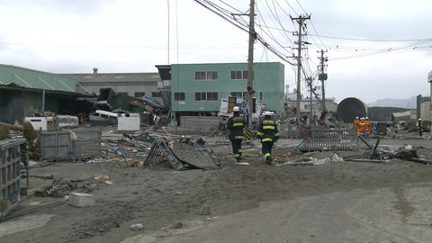 Fire Crew Walks Through Area Destroyed By Tsunami In Japan stock footage
