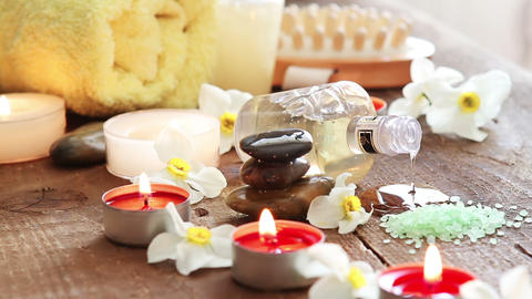Spa still life of massage oil , towel , rocks and flowers 2 Live Action