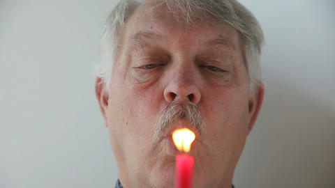 Man Is Unable To Blow Out Candle stock footage