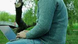 Male hands typing on laptop in the park Footage