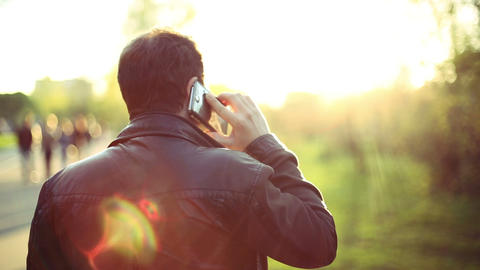 Man calling on mobile Phone at Sunset in park. View from the back. Man talking o Footage