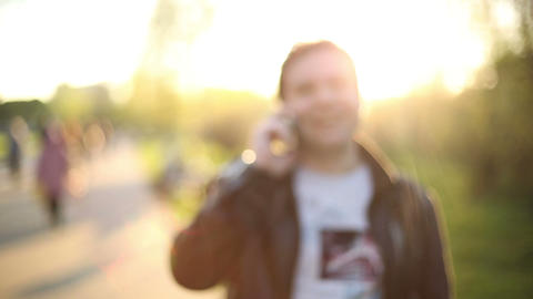 Man talking on Smartphone at Sunset in park. Blur. Out of Focus. HD 1080 Footage