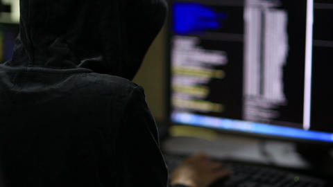 Hacker in hood cracking code using laptop and computers from his dark hacker roo Live Action