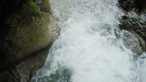 Adult men dropped by the tour lieder into waterfall on canyoning expedition Footage