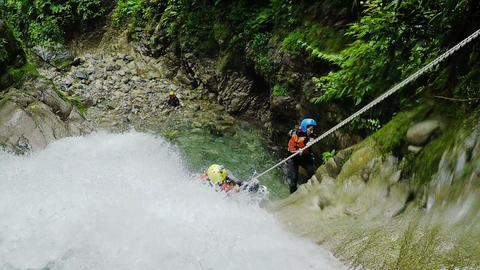 Adult tourist couple rappelling into large waterfall Footage