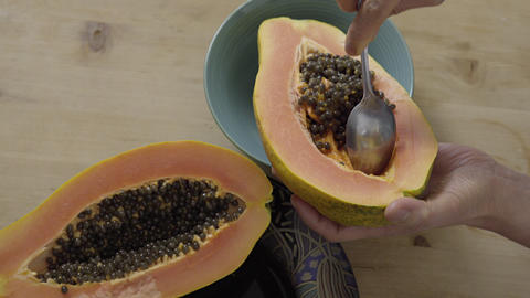 Scooping out the seeds from a Papaya 4K UHD Footage