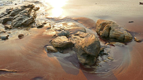ocean shore with purple granite sand at sunset Footage