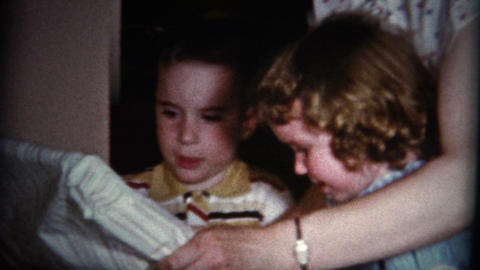 (8mm Vintage) Kids and Mom Opening Christmas Gift Footage