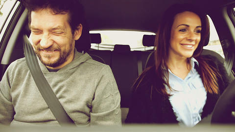 Man driving car with girlfriend talking about funny things laughing Footage