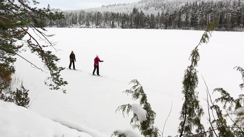 Couple skiing in a snowy landscape at a frozen lake in Finland Footage