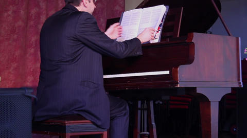 Pianist sits down by by the piano and starts playing Live Action