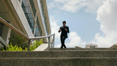 Chinese Businessman Going Downstairs Sliding On Rail For Joy stock footage