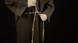 Friar dressing tying knot in habit sackcloth Footage