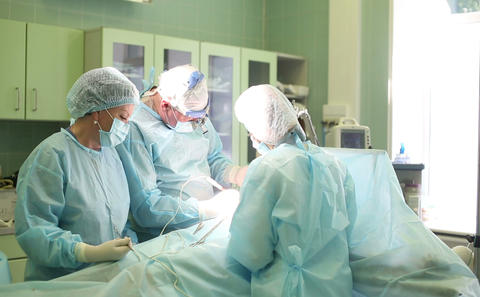 Surgeon performing cosmetic surgery on breasts in hospital operating room. Mammo Footage
