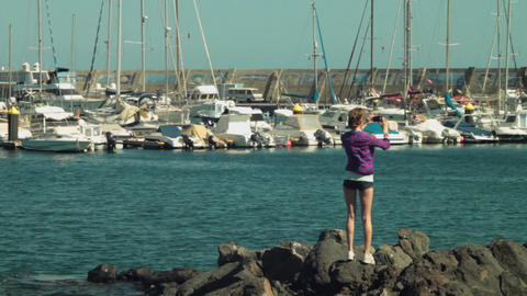 long shot of blond girl model shooting panoramic video photo a of yacht club OE Footage