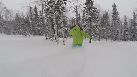 Snowboarder girl rides in powder snow Footage