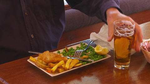 man enjoys a beer with fish & chips Footage
