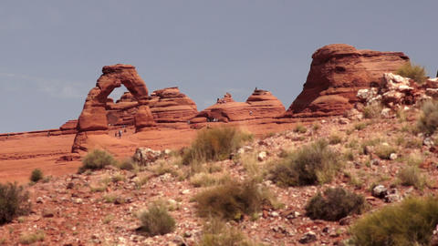 People move around Delicate Arch exploring the desert landscape Live Action