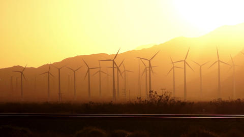 The Sun sets on Wind Turbines generate energy that goes across the mountains to  Footage