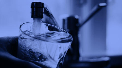 Glass Is Filled With Tap Water And Is Overflowing stock footage