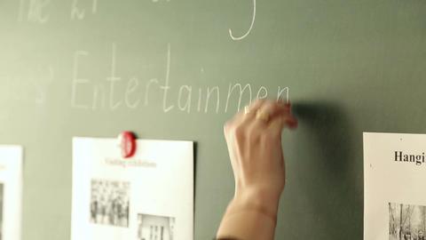 The teacher writes on the blackboard at school Footage