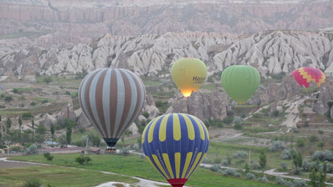 Multi-colored balloons fly over rocks Live Action