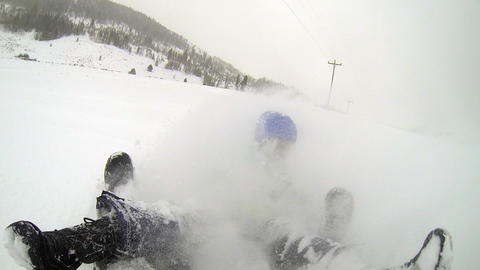 GoPro shot snow tubing down fast hill as snow sprays over tuber Live Action