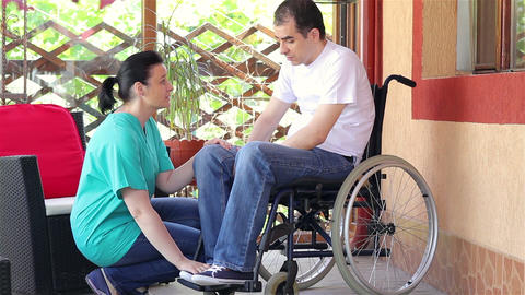 Female Nurse Consoling Sad Man Sitting In Wheelchair stock footage