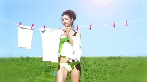 Beautiful young woman hangs laundry on a background summer landscape Live Action