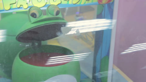 Arcade game machine at an amusement park, green frog Footage