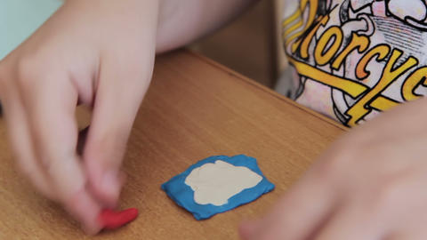 Child moulds from plasticine on table Footage