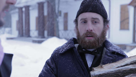 bearded man in clothes of 19 centuries with wood in his hands, Russian winter Footage